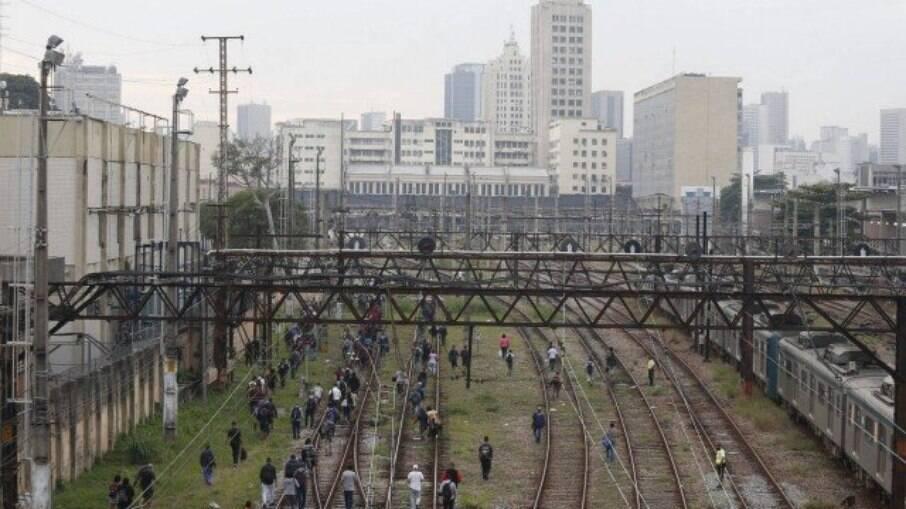 Passageiros andam na linha do trem após protesto