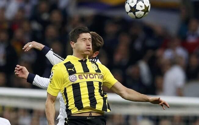 O atacante do Borussia, Robert Lewandowski,  tenta ganhar de cabeça da defesa do Real Madrid