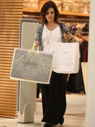 Fátima Bernardes saindo de uma loja de roupas masculinas: presente para Bonner?