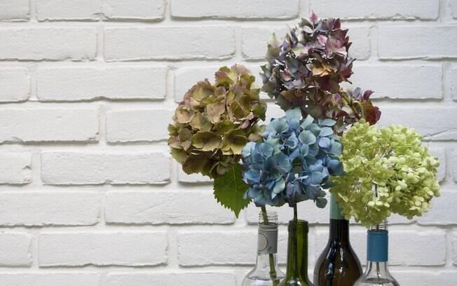 As garrafas são itens versáteis e, com diversos formatos e tamanhos à disposição, vale investir nas flores para decorar