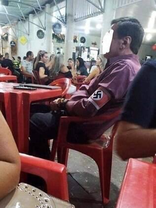 Homem sentado em cadeira de bar com uma braçadeira com o símbolo nazista