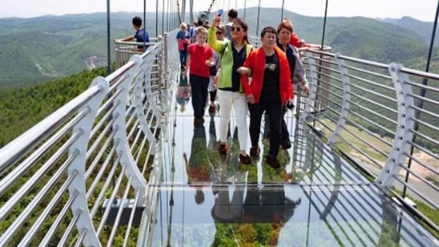 Turistas na ponte da montanha Piyan