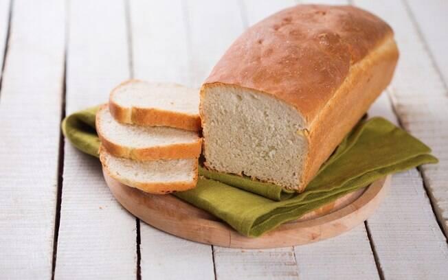 Pão integral fatiado em cima de uma tábua de madeira