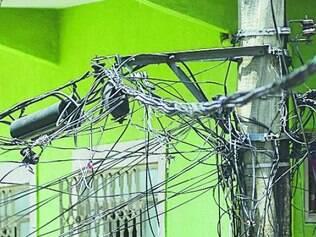 Emaranhado.  Proximidade de fios elétricos com os de TV, internet e telefone provoca perdas