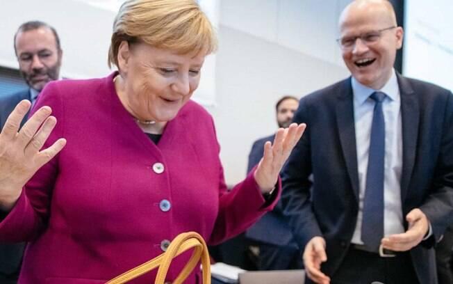 Angela Merkel não pôde apertar a mão de ministro e levantou-as em sinal de saudação