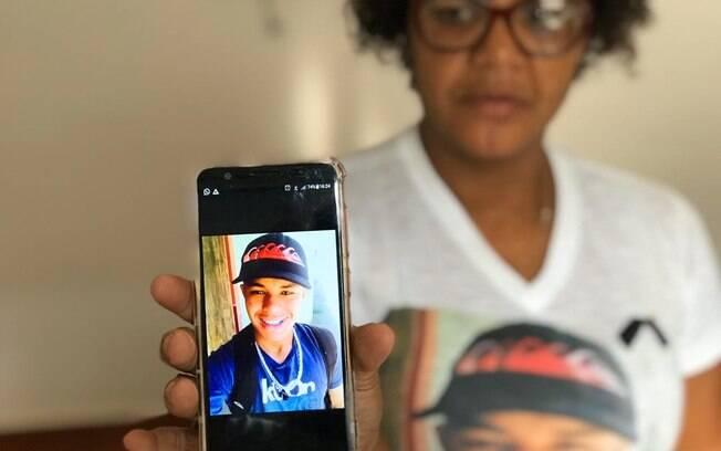 mulher segurando celular com foto de menino dentro