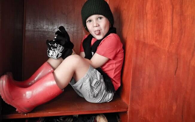 Aos 4 anos, Théo gosta de usar cachecol, luvas e gorro, mesmo no calor. A mãe, Roberta Catani, está ajudando-o a entender os códigos sociais e a funcionalidade das roupas