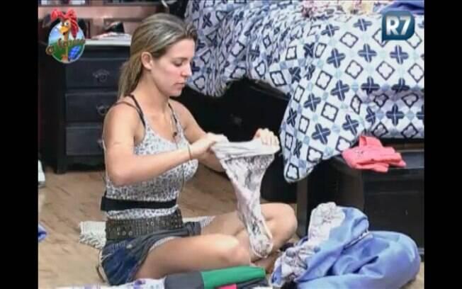 Joana organiza as roupas no baú