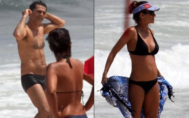 Eduardo Moscovis mergulha no mar enquanto Cynthia Howlett se prepara para deixar a praia
