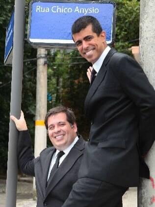 Leandro Hassum e Marcius Melhem posam em frente à nova cidade cenográfica do programa, homenagem a Chico Anysio