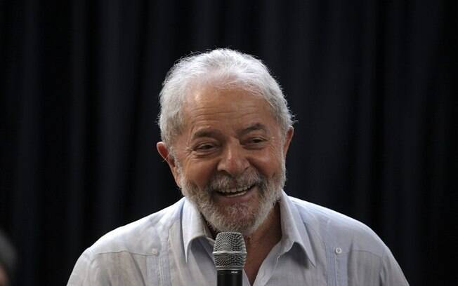 homem sorrindo e com microfone na mão