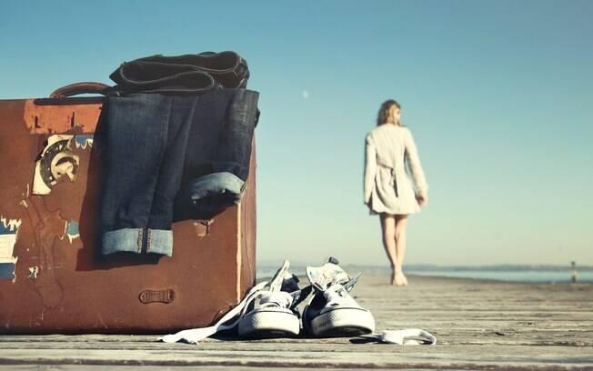 Garota andando descalça afastando-se de suas malas