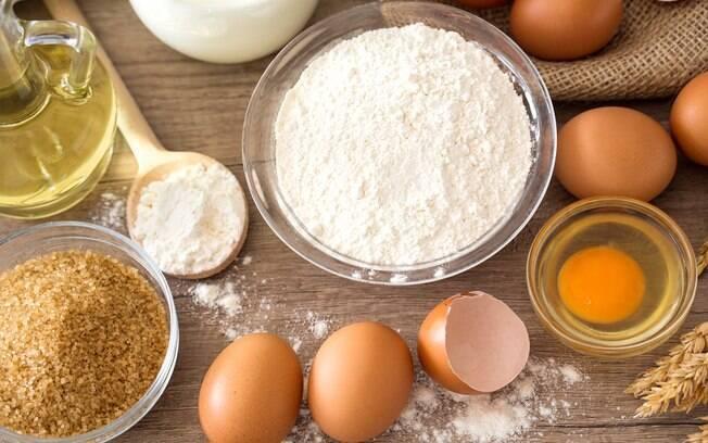 farinha, ovos e fermento em uma mesa de madeira