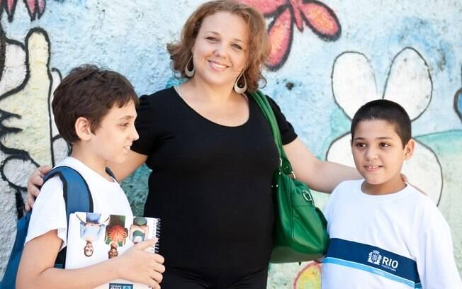 Cris e os filhos em frente à escola: mudança da particular para a pública, depois do susto, foi uma boa surpresa