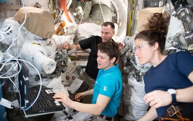 Acompanhadas por Nick Hague, Anne McClain e Christina Koch trabalham na manutenção do traje espacial da Nasa