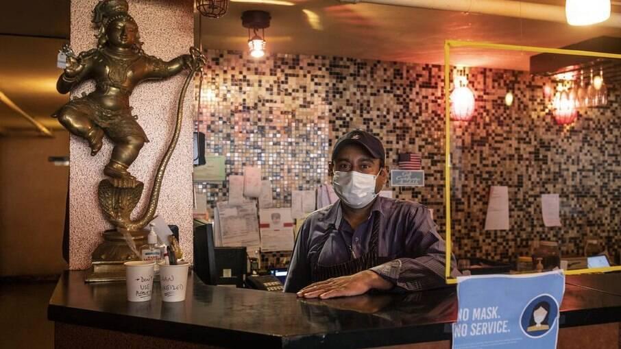 Funcionário de um restaurante no Queens ao lado de uma barreira de plástico anti-covid
