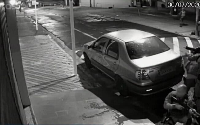 imagem de pessoas escondidas atrás de carro