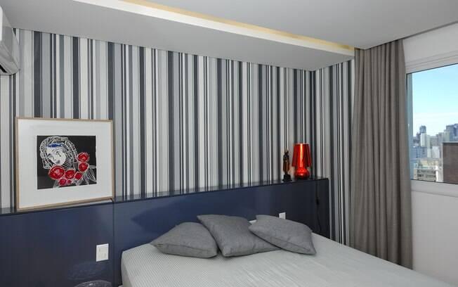 O papel de parede com as listras em preto e branco conferem personalidade e ousadia para o quarto