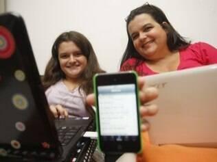 Ana Luiza e a mãe, Christiana, entre celular e laptops: pais precisam conhecer o universo virtual para regular o acesso dos filhos