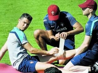 Com cara de poucos amigos, o craque Cristiano Ronaldo deixou o campo de treino mais cedo e usando uma proteção no joelho esquerdo