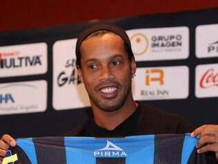 Brazil's Ronaldinho holds up his new Queretaro soccer club jersey at a press conference in Mexico City, Friday, Sept. 12, 2014. Mexican first-division club Queretaro signed the former 34-year-old soccer star, who had been without a club since leaving Brazil's Atletico Mineiro in July and had been negotiating with several clubs. The two-time FIFA world player of the year helped Atletico Mineiro win last year's Copa Libertadores for the first time. (AP Photo/Marco Ugarte)