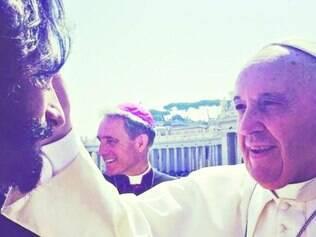 Papel. Rodrigo Santoro, que está com cabelos e barba grandes para viver Jesus Cristo, recebendo a bênção