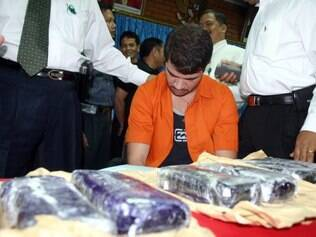 Brazilian Rodrigo Gularte (C) is presented to the media along with seized six kilograms (13.2 pounds) of cocaine at the Customs office of Sukarno-Hatta airport in Tangerang, 05  August 2004.  Gularte was arrested 31 July for attempting to smuggle a large quantity of cocaine into Indonesia hidden inside a surfboard.  AFP PHOTO