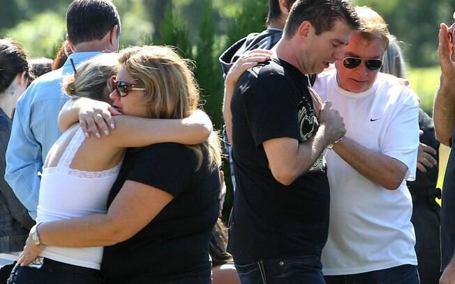 Gladimir Callegaro (2º à D), pai da vítima Marina Callegaro, e outros parentes choram durante seu enterro em cemitério na cidade de Santa Maria (28/1)