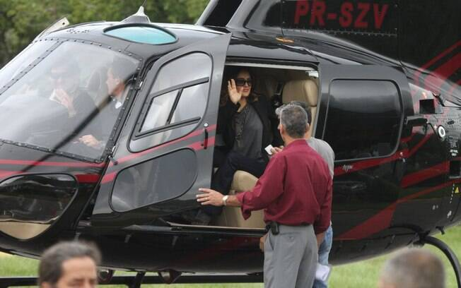 Salma Hayek acena para seus fãs antes de decolar
