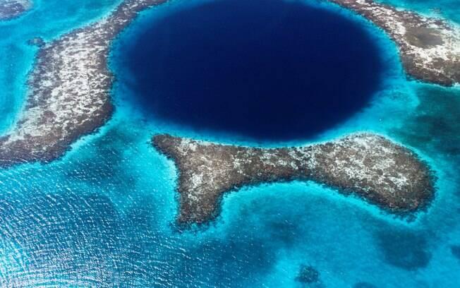 O Great Blue Hole, em Belize, parece um grande buraco coberto de água e tecnicamente é e atrai muitos mergulhadores