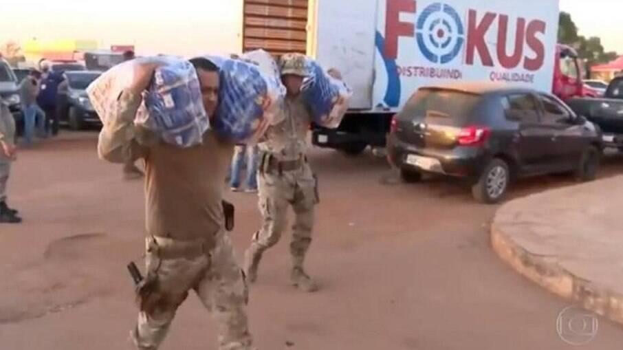 Policiais levam as doações até a escola usada como base