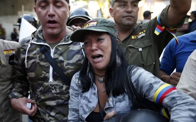 Venezuelanos choram após o anúncio da morte do presidente Hugo Chávez em Caracas (05/03)