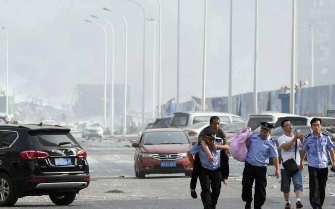Morador de Tianjin recebe ajuda de um policial chinês para ir a um local seguro após explosões do dia anterior