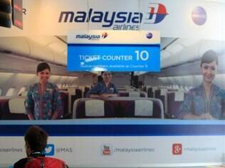 A passenger checks information at a Malaysia Airlines booth at Kuala Lumpur International Airport in Sepang, outside Kuala Lumpur, Malaysia, Saturday, March 8, 2014. A Malaysia Airlines Boeing 777-200 carrying 239 people lost contact with air traffic control early Saturday morning on a flight from Kuala Lumpur to Beijing, and international aviation authorities still hadn't located the jetliner several hours later. (AP Photo/Lai Seng Sin)