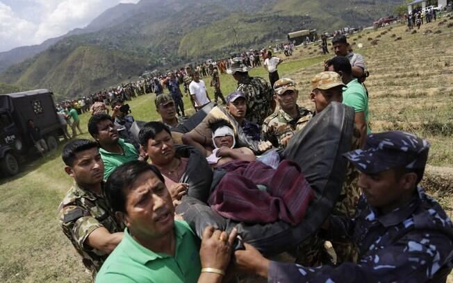 Soldados nepaleses transportam ferido em maca improvisada para helicóptero da força aérea indiana