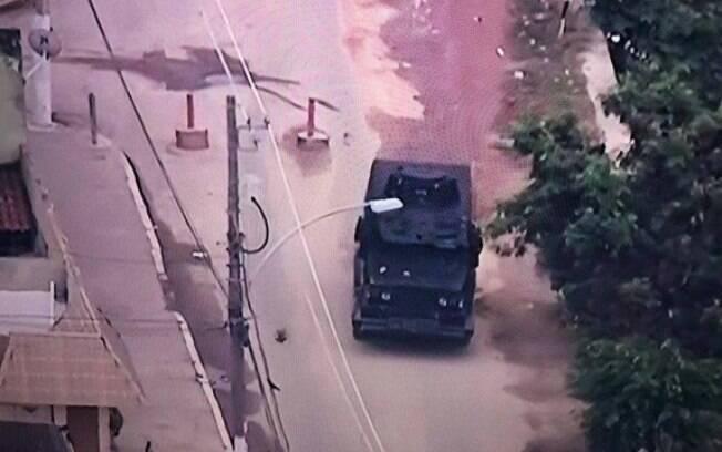 Momento em que um blindado da PM passa por uma barricada na Cidade de Deus