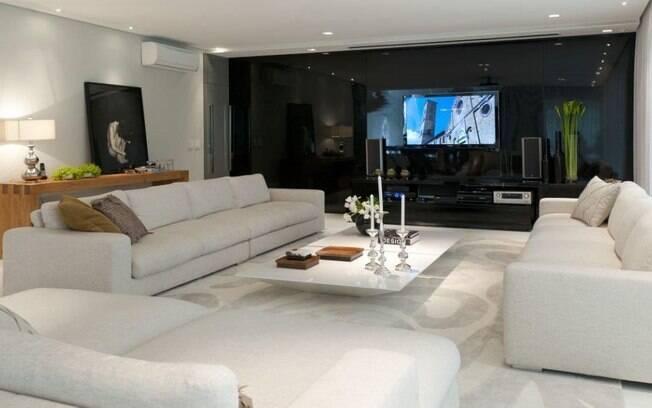 O living planejado por Consuelo Jorge conta com um home theater instalado dentro de um painel de vidro negro