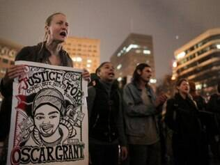 OAKLAND, CA - DECEMBER 3: Jessica Long of San Francisco holds a 'Justice for Oscar Grant' poster during a demonstration following a Staten Island, New York grand jury's decision not to indict a police officer in the chokehold death of Eric Garner on December 3, 2014 in Oakland, California. The store was vandalized and looted last week during protests. The grand jury declined to indict New York City Police Officer Daniel Pantaleo in Garner's death.   Elijah Nouvelage/Getty Images/AFP