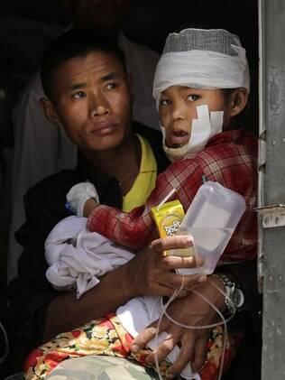 Soldado nepalês ajuda criança ferida após serem retirados de área no Nepal e esperam para desembarcar do helicóptero da Força Aérea do país na Índia