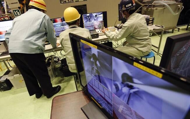 Trabalhadores assistem a monitor que mostra imagens ao vivo transmitidas a partir de um robô controlado por controle remoto no Japão (5/02)