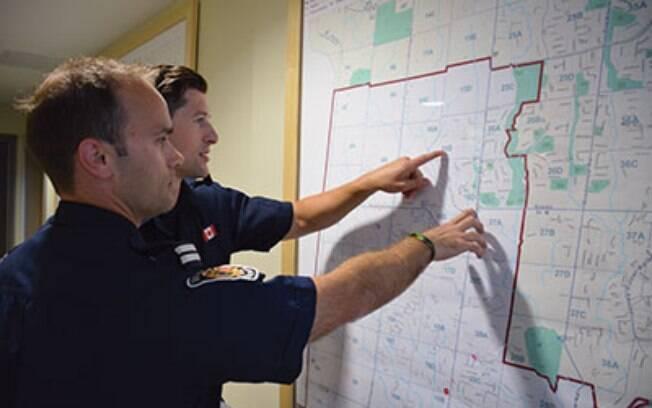 Bombeiros veem área de incêndio em mapa de papel em Ontario, Canadá: técnicas ultrapassadas