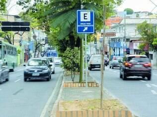 Sinalização. Placas no canteiro central e nas calçadas da avenida indicam onde há vagas de rotativos