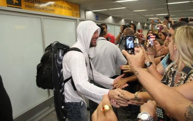 ... posar para as fotos dos fãs que o aguardavam no aeroporto internacional do Rio de Janeiro