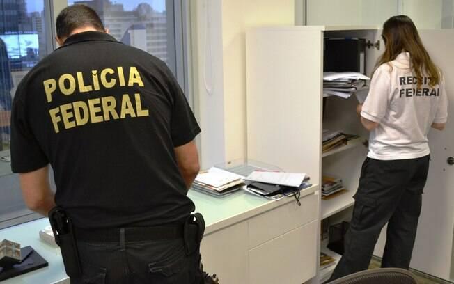 Agentes da Polícia Federal investigam documentos apreendidos durante a Operação Lava Jato