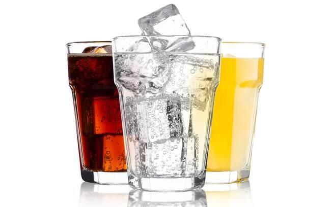 Copos de refrigerantes e água com gás sobre fundo branco