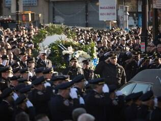 NEW YORK, NY - DECEMBER 27: Officers salute outside the church following the funeral of slain NYPD officer Rafael Ramos at the Christ Tabernacle Church in the Glenwood section of Queens, NY. Ramos was shot, with his partner Police Officer Wenjian Liu, last Saturday while sitting in their police car.   Kevin Hagen/Getty Images/AFP