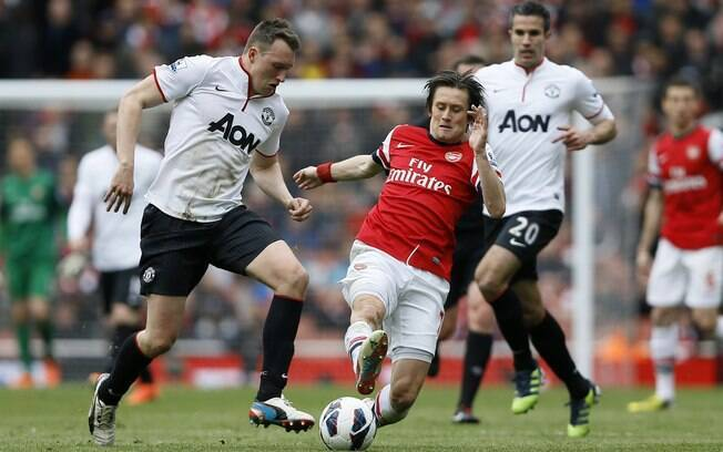 Phil Jones e Rosicky disputam a bola durante  jogo entre Manchester United e Arsenal