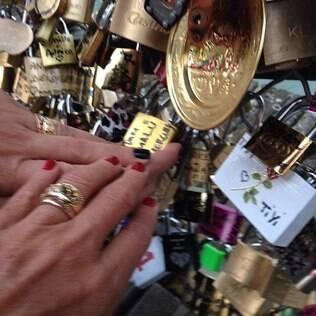 O casal coloca seu cadeado na Pont des Arts