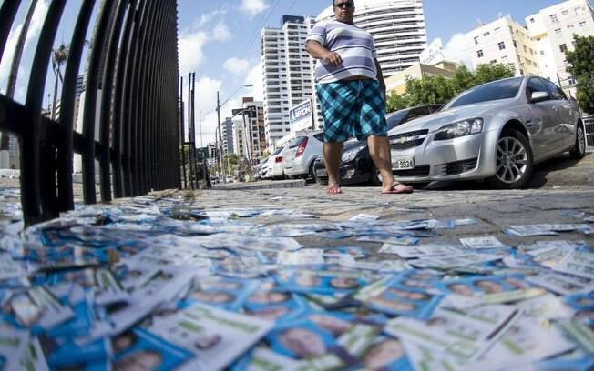 Homem passa por rua repleta de santinhos em Fortaleza; panfletagem no dia das eleições é um dos crimes eleitorais mais comuns