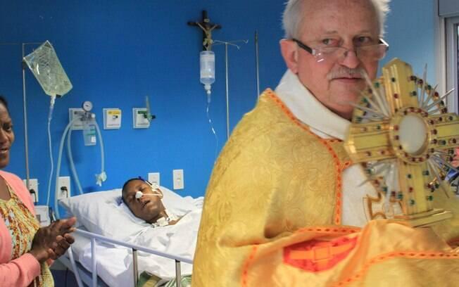 O padre Samiro Meurer visita pacientes e funcionários do Hospital São José durante procissão de Corpus Christi, em Criciúma (SC), nesta quinta-feira (30). . Foto: Ulisses Job/Futura Press